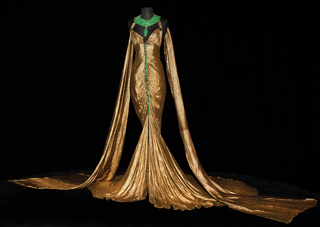 long gold dress, with long sleeves down to the floor, emerald green accents